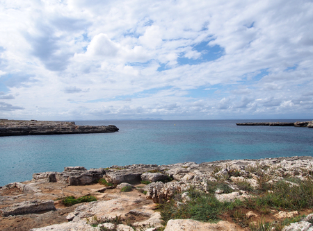 clifftop view of the cove at cale santandria in menorca with rocky shore and blue summer sea with white clouds