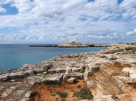 a scenic view of the bay at cala santandria in menorca with carved cliffs and old fort in the distance with blue summer sky