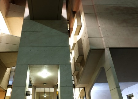 close up details of the entrance of a modern geometric building illuminated at night with shadows and walkways