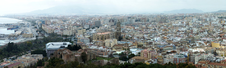 wide panoramic aerial view of the city of malaga in spain with historic landmarks and urban buildings down to the sea and harbor Stock Photo