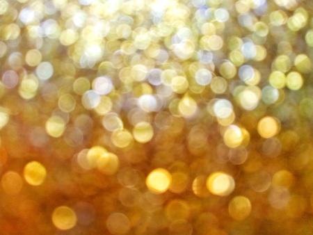 Blurred gold sparkling glitter lights graduated background