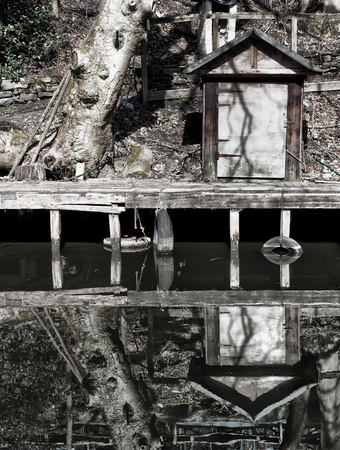 a waterside run down wooden jetty with a small shack and tree reflected in the still water