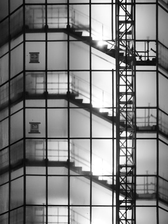 monochrome image of a staircase in a tall high-rise building on a construction site at night with a tower hoist and scaffolding illuminated by bright lights