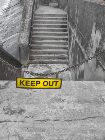 yellow keep out sign on a metal chain blocking some concrete steps