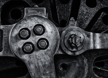 close up of the wheel and coupling rods of an old steam locomotive with textured metal surface and bolts