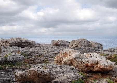 rugged coastal rocks against a the sea with and white clouds in menorca spain travel or vacation background Stock Photo