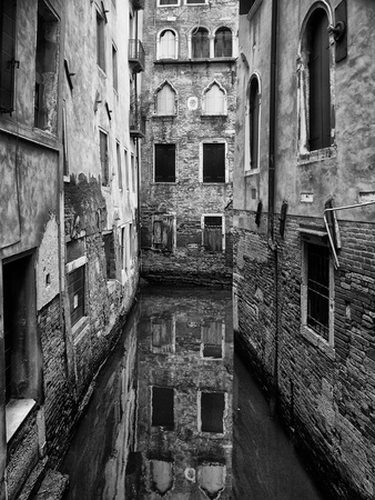 dark monochrome image of a quiet narrow canal in venice surrounded by picturesque ancient buildings reflected in the water