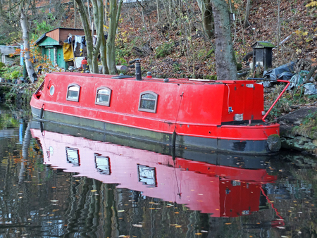 a red narrow boat reflected in still water on the rochdale canal in hebden bridge surrounded by autumn trees and sheds