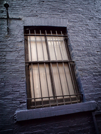 slanted image of an old metal window with metal bars in a black painted wall Stock Photo