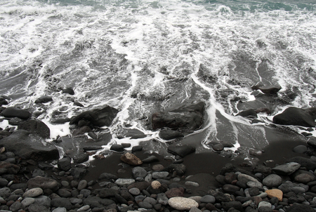 white surf breaking on a black sand beach with colored pebbles and stones in puerto de la cruz tenerife Stock Photo