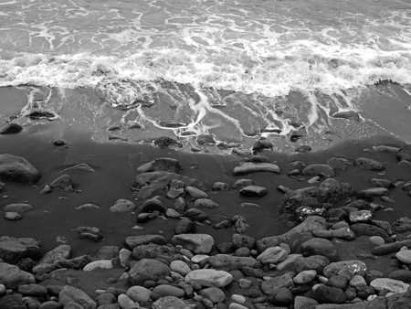 monochrome image of white surf breaking on a black sand beach with colored pebbles and stones in puerto de la cruz tenerife