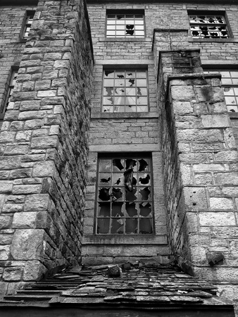 a monochrome image of broken windows in an empty abandoned vandalized old stone building Stock Photo