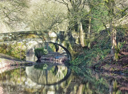 an old stone bridge reflected in the water surrounded by sunlit woodland on the rochdale canal near hebden bridge in west yorkshire