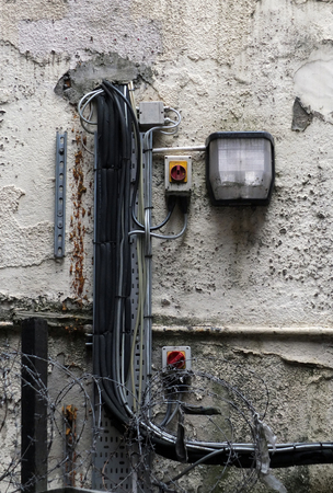 an external security light mounted on an old shabby external wall with messy wiring and barbed wire