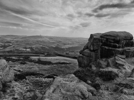 a monochrome image of a large stone outcrop known as great rock in todmorden west yorkshire with overcast sky and pennine lansdcape