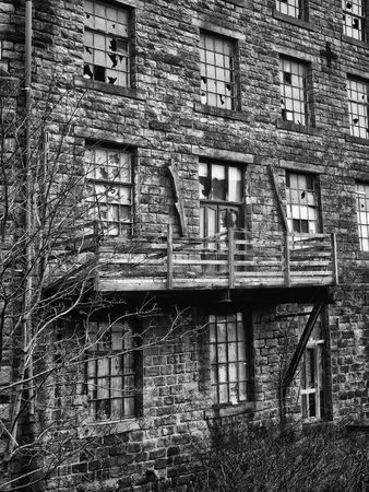 monochrome image of an old abandoned stone factory building