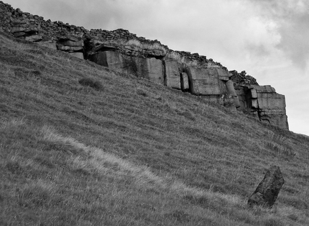 a monochrome image of a large stone outcrop with round stone wall on a hillside with a standing stone in the yorkshire dales