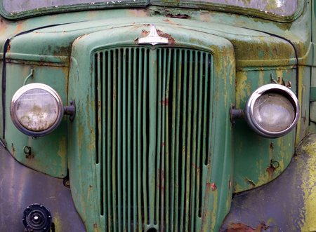 close up of the front of an old abandoned rusting green truck covered in moss