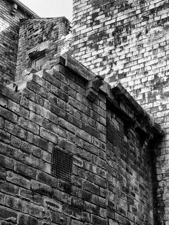 monochrome image of old stained weathered brick walls at the rear of old houses Stock Photo