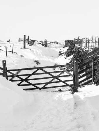 a monochrome image of a snow covered country lane with wooden gates and surrounding fields and moors