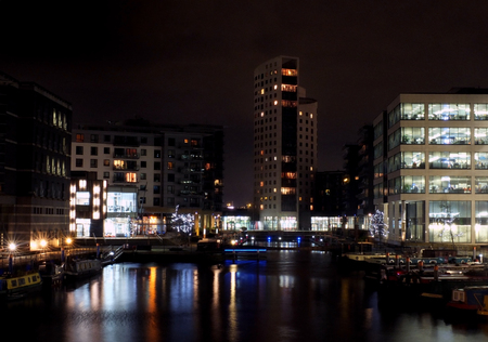 a view of clarence dock in leeds at night with waterside buildings and lights reflected in the water
