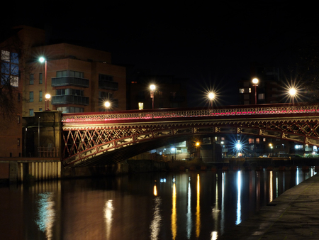 crown point bridge crossing the river aire in leeds at night with lights and surrounding buildings reflected in the water