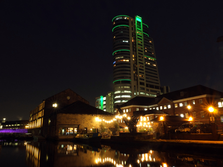 leeds canal wharf at night with brightly illuminated buildings and lock reflected in the water and bridgewater place glowing against a dark sky Stock Photo
