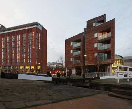 leeds, england - 24 january 2019: the doubletree hilton hotel in leeds next to the dock and canal lock gates with apartment developments illuminated at twilight