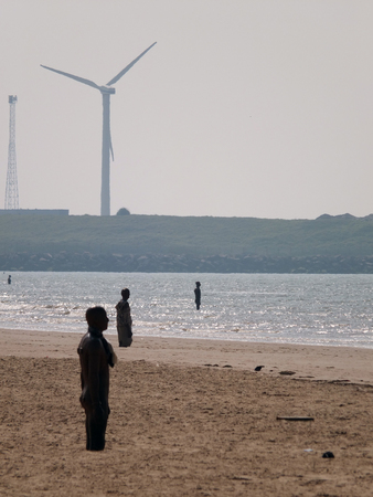 Crosby, England - 13 july 2017: crosby beach with large wind turbine and anthony gormleys another place installation