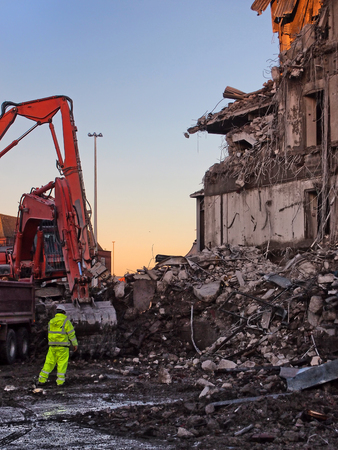unidentifiable man in high visibility clothing working in front of an orange excavator on the demolition site of a large building with collapsing walls and rubble