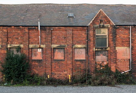 An old abandoned brick factory building with boarded up windows and crumbling decaying walls overgrown with weeds Imagens - 117775252