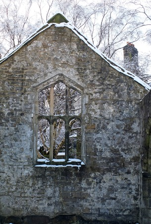 view through a window in the wall of a medieval ruined church in heptonstall yorkshire with snow covered trees behind the stone frame
