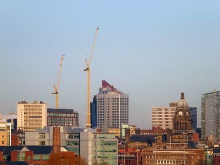 A long panoramic view of leeds showing the town hall offices apartments and skyscrapers with construction cranes with sunlit blue sky Stock Photo