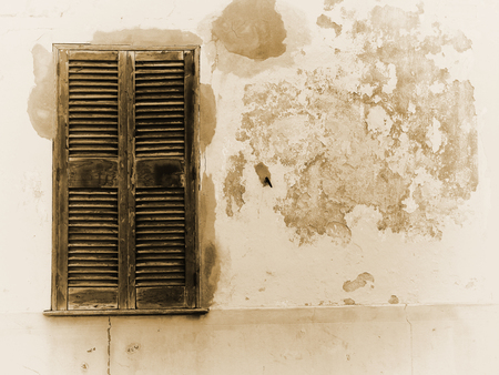 faded sepia image of an old cracked house wall with patched cement painted in flaking peeling layers of paint with a wooden cracked window with closed shutters