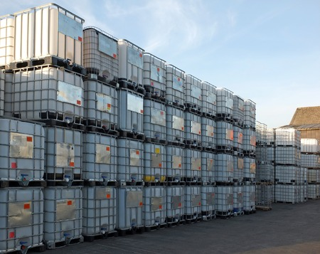 used metal framed intermediate bulk containers stacked on pallets waiting to be cleaned or recycled in an industrial yard Reklamní fotografie