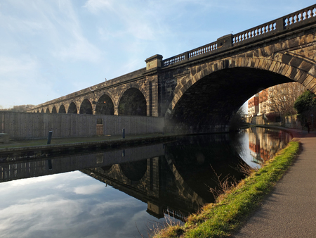 Old abandoned railway viaduct crossing the canal in leeds city centre near whitehall road with arched reflected in the water