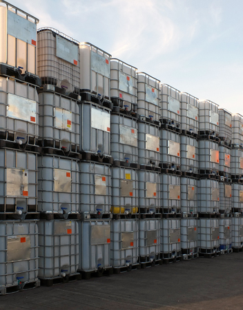 metal framed intermediate bulk containers stacked on pallets waiting to be cleaned or reused in an industrial yard
