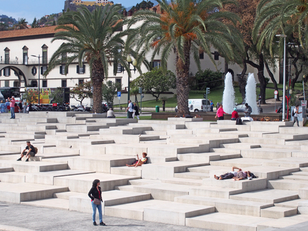 Funchal, Madiera, Portugal - 15 march 2019: tourists sitting and passers by on the concrete steps of the marina in funchal facing the old town with historic buildings and traffic on the road