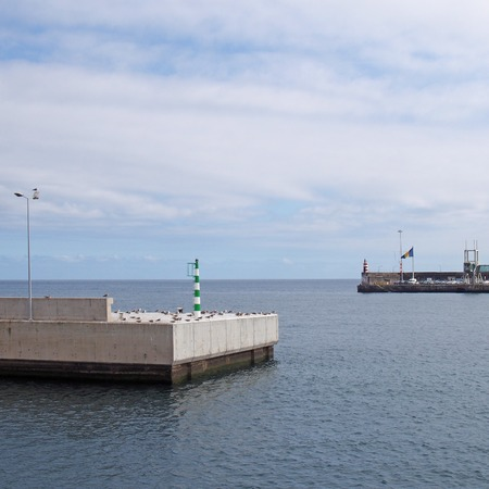 the entrance to funchal harbour in madeira with safety lights and flags on the end of the concrete piers with blue calm sea and sunny white clouds Zdjęcie Seryjne