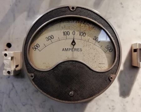 a large round vintage industrial ammeter with an analogue dial with numbers with standard electrical symbols on a white dial on a grey background