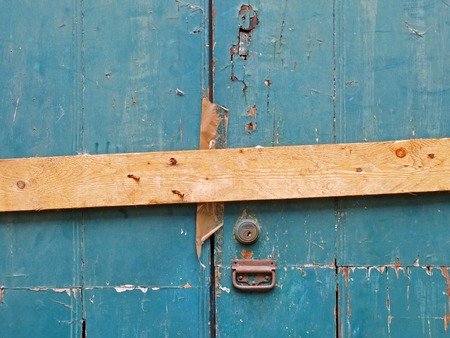 close up of an old peeling green painted wooden plank door barred shut with a piece of timber and rusty nails with a lock and handle Stock Photo