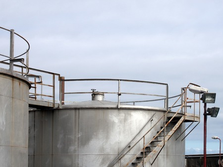 the top of large old silver steel industrial storage tanks with control valves rusting stairs and walkway against a blue sky