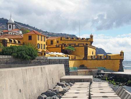view of the 17th century yellow fort Fort of São Tiago in funchal madeira taken from the seafront with sunlit blue sea and boats with the hills surrounding the city in the distance