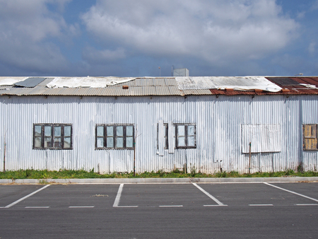 an old abandoned white industrial building with rusting patched repaired corrugated roof and boarded up windows