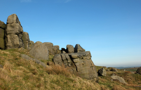 large rugged gritstone outcrop at the bridestones a large rock formation in west yorkshire near todmorden with blue sunlit sky