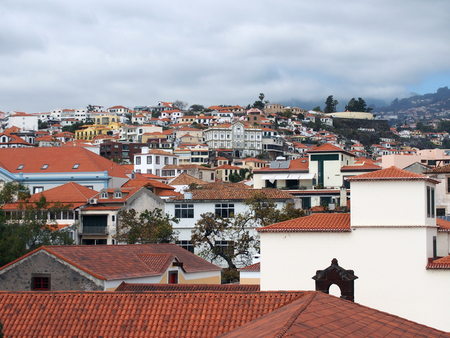 a panoramic cityscape view of funchal showing roofs and buildings of the town cente and cloudy sky