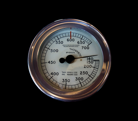 an old round metal industrial tachometer on a black background with numbers marked on a white dial