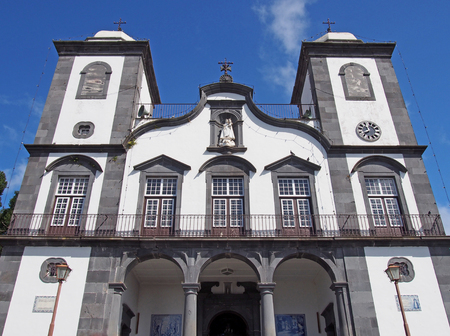 front view of the historic Church of Our Lady of Monte - Igreja de Nossa Senhora do Monte in funchal in bright sunlight with blue sky