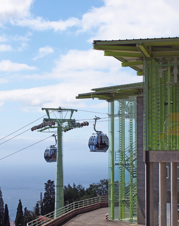 funchal, madeira, portugal - 13 march 2019: gondolas outside the overhead cable car station in monte running from funchal in madeira with blue sky and sea in the background