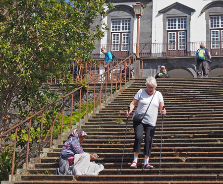 funchal, madeira, portugal - 14 march 2019: a tourist walking around an old lady begging on the steps of the historic Church of Our Lady of Monte in funchal